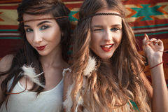 Two beautiful happy girls sending kiss and wink over ecthic back. Ground Royalty Free Stock Photos