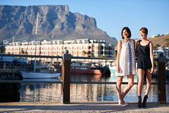 Two beautiful happy girls smiling in front of table mountain. Two women standing next to each other while looking off camera with water and a beautiful view Royalty Free Stock Photo