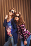 Two beautiful happy girls in sunglasses on the urban background. Royalty Free Stock Image