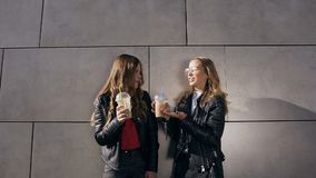 Two beautiful happy girls talking and drinking cocktails while standing near gray wall beside modern building. Outdoors stock video footage
