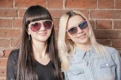 Two beautiful happy girls in trendy sunglasses on the urban background or red brick wall. Young hipster people. Outdoors portrait. Stock Photo