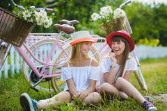 Two beautiful happy hipster girls laughing with bikes. Two beautiful happy hipster girl with bikes. teenagers laughing and posing for the camera Royalty Free Stock Photos
