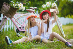 Two beautiful happy hipster girls laughing and posing for the camera with bikes. Two beautiful happy hipster girl with bikes. teenagers laughing and posing for Stock Images