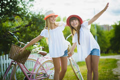 Two beautiful happy hipster girls laughing and posing for the camera with bikes. Two beautiful happy hipster girl with bikes. teenagers laughing and posing for Stock Photo