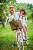 Two beautiful happy hipster girls laughing and posing for the camera with bikes. Two beautiful happy hipster girl with bikes. teenagers laughing and posing for Stock Photography