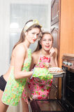 Two beautiful happy smiling & looking at camera young pinup women in aprons baking cake. Two beautiful pinup women in aprons baking cake Stock Photography