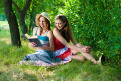 Two Beautiful happy smiling young women reading Stock Photo
