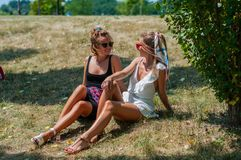 Two beautiful happy women on the grass relaxing outdoors in summer. royalty free stock images