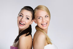 Two beautiful happy women leaning on each other back Royalty Free Stock Photo