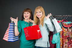 Two beautiful happy women with shopping bags in the clothes store. Stock Photos