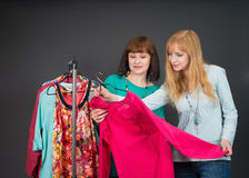 Two beautiful happy women with shopping bags in the clothes store. Stock Images