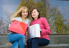 Two beautiful happy women with shopping bags near clothes store. Stock Images