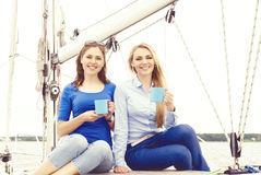 Two beautiful, happy and young girls enjoying a good summer day on a yacht and having a tea. Vacation, holiday and traveling concept Royalty Free Stock Images