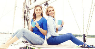 Two beautiful, happy and young girls enjoying a good summer day on a yacht and having a tea. Vacation, holiday and traveling concept Stock Photography