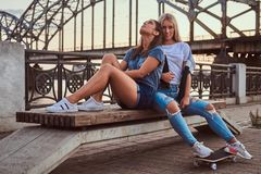 Two beautiful hipster girls sitting on the bench on a background of the skyscraper. royalty free stock photos