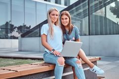 Two beautiful hipster girls sitting on the bench with a laptop on a background of the skyscraper. stock photos