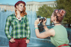 Two beautiful hipster girls taking pictures on film camera outdo Royalty Free Stock Photo