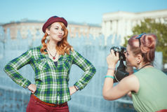 Two beautiful hipster girls taking pictures on film camera outdo Stock Photos
