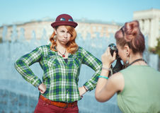 Two beautiful hipster girls taking pictures on film camera outdo Stock Image