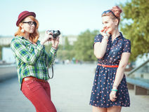 Two beautiful hipster girls taking pictures on film camera outdo Royalty Free Stock Images