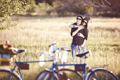 Two beautiful hipsters standing outdoor. In summer with white vintage fixed gear bicycle royalty free stock photography