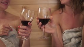 Two beautiful hot sexy girlfriends women drinking red wine from glasses and chatting in wooden finnish Sauna wet from. Steam - Party night - Business women stock footage