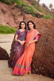 Two beautiful indian woman in beautiful traditional saree at sunset stock photo