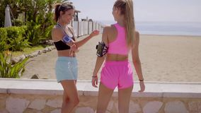 Two beautiful joggers talk and stretch by wall. Two beautiful joggers talk and stretch by stone wall before going on a run near the beach on a nice summer day stock footage