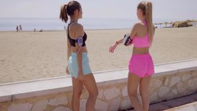 Two beautiful joggers talk and stretch by wall. Two beautiful joggers talk and stretch by stone wall before going on a run near the beach on a nice summer day stock video footage