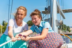Two beautiful and joyful girls pull a rope on a yacht on the deck, laugh and joke. stock image