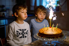 Two beautiful kids, little preschool boys celebrating birthday and blowing candles Royalty Free Stock Photos