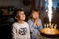 Two beautiful kids, little preschool boys celebrating birthday and blowing candles Royalty Free Stock Photo