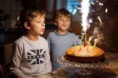 Two beautiful kids, little preschool boys celebrating birthday and blowing candles on homemade baked cake, indoor. Birthday party for siblings children. Happy royalty free stock photography