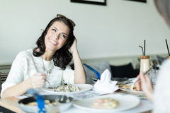 Two beautiful ladies eating in a restaurant while having a conve Stock Photo
