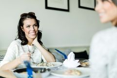 Two beautiful ladies eating in a restaurant while having a conve Royalty Free Stock Images