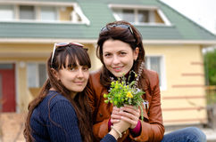 Two Beautiful Ladies Holding Flowers Royalty Free Stock Photos