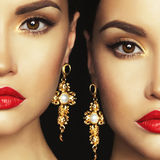 Two beautiful lady with earrings on black background Stock Photography