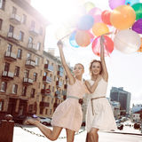 Two beautiful ladys in retro outfit holding a bunch of balloons Royalty Free Stock Photos