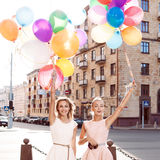 Two beautiful ladys in retro outfit holding a bunch of balloons Stock Image