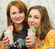 Two beautiful laughing girls drink cocktails Stock Photography
