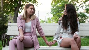 Two beautiful lesbian women feel shy, sitting on a bench and join hands. LGBT concept stock video footage