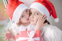 Two beautiful little girls with Christmas gifts Stock Photos