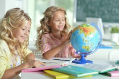 Two beautiful little girls at class reading book and  looking at. Globe Stock Images