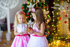 Two beautiful little girls give each other gifts. In a festive interior. On a background a set of bright sparks. Waiting for a holiday Royalty Free Stock Photos