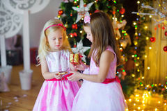 Two beautiful little girls give each other gifts. In a festive interior. On a background a set of bright sparks. Waiting for a holiday Stock Photography