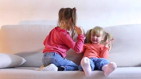 Two beautiful little girls play and fun to spend time on couch. Two small friends playing on sofa in living room, children jump, have fun and laugh happily stock video