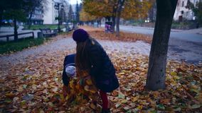 Two beautiful little girls playing with leaves in autumn evening. HD stock video