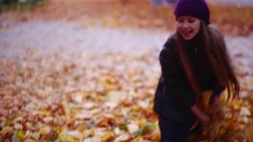 Two beautiful little girls playing with leaves in autumn evening. HD stock footage