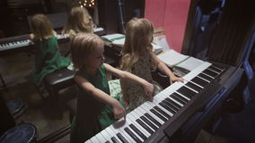 Two beautiful little girls are playing piano in a room. Friendship and music. Two beautiful little girls are playing piano in a room. Little blondies are stock video footage