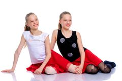 Two beautiful little girls are sitting on the floor in the studi. Two cute little girls are sitting on the floor in a studio on a white background. Concepts of Royalty Free Stock Photos